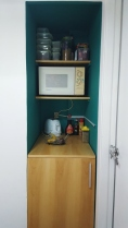 Pantry box, now arranged with built-in shelves and an open-air design to match its opposite shelves. Hidden storage of pots and pans.